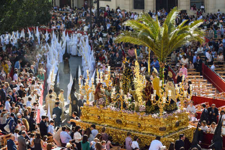 A large group of traditionally dressed up Nazarenes are leading the Easter processions, and the enormous sculpture of Jesus Christ and virgin Maria is being carried after.