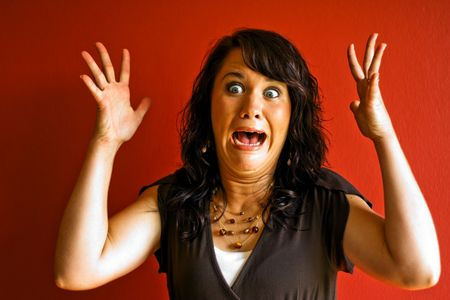 Young attractive beautiful brunette woman hands up and surprised scared