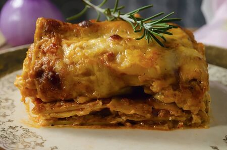 Chicken lasagna, on a golden plate decorated