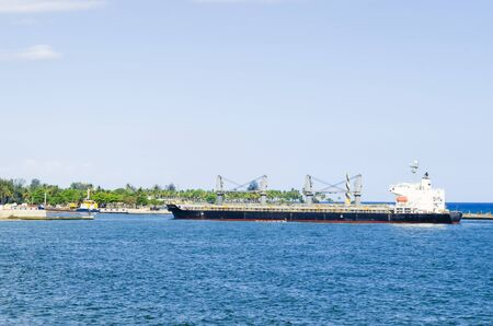 cargo boat arriving at the entrance of the port of Santo Domingo, Dominican Republic with a tropical blue sea and clear and warm skies