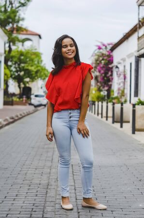 Outdoor portrait of young beautiful girl 19 to 25 years old. Brunette. posing in the middle of a colonial street with cobblestones. Wearing red blouse City lifestyle. Female fashion concept.