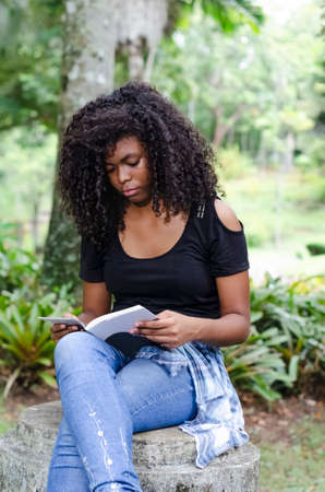 a young black woman between 20 and 30 years old sitting reading a book alone, in a park, surrounded by trees 免版税图像