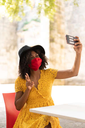 young black woman with curly hair, with red mask, yellow dress and black hat, checking her phone
