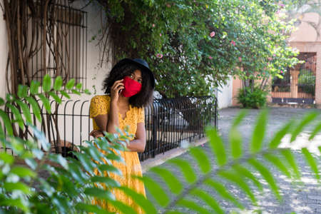 young black woman with curly hair, with a red mask, yellow dress and black hat, talking with her smart phone happy Standard-Bild