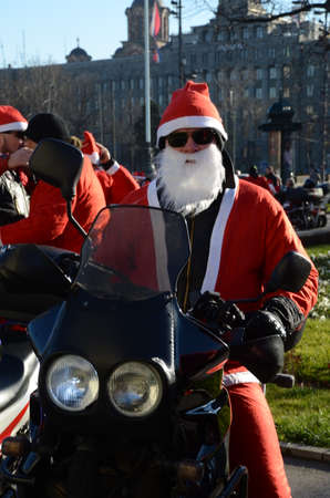 ni�o discapacitado: BELGRADO, SERBIA - 27 de diciembre: Indefinido Santa entregar ayuda humanitaria en forma de regalos a los ni�os discapacitados en la motocicleta anual desfile de Pap� Noel el 27 de diciembre de 2014 en Belgrado, Serbia
