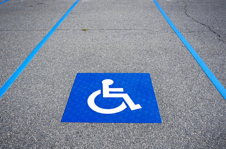 diagonal stripes: International handicapped symbol painted in bright blue on a shopping center parking space. The space is clearly marked on either side with additional white diagonal stripes.