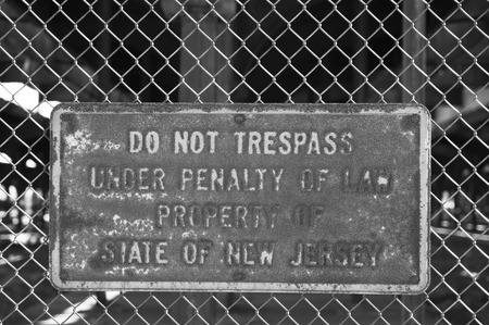 No trespassing sign on the fence, warning about penalty of law photo