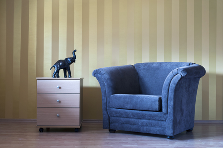 Modern interior room with sofa chair and stripes wall and elephant sculpture