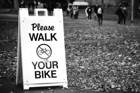 Please Walk ypur bike sign in city park photo