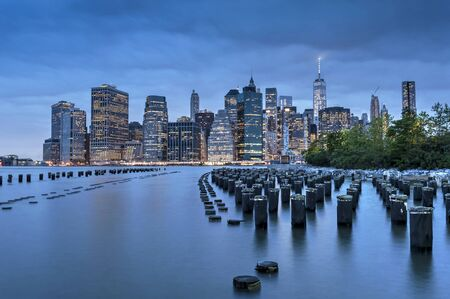 finacial: New York City Manhattan Finacial District panorama at dawn with skyscrapers illuminated over east river Stock Photo