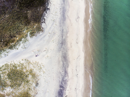 Abstract Aerial View of Sandy Beach and Small Waves from Above