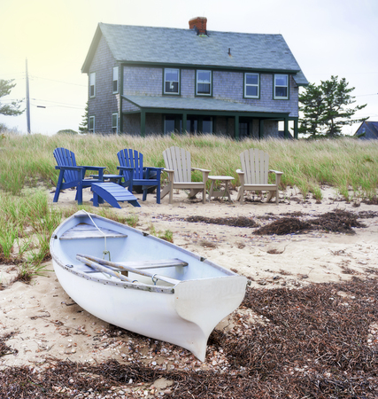 NANTUCKET ISLAND, MASSACHUSETTS, USA -  OCTOBER 5: Beach house at the end of summer with boat and chairs on sandy beach, Nantucket Island on October 5, 2018.