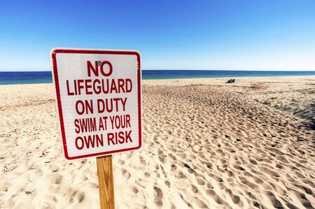 No Lifeguard on Duty Sign on Sunny day in Summertime at Sandy Beach. You swim at your own risk.