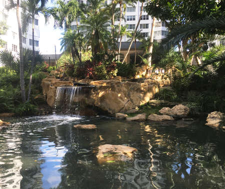 beautiful place in the city with a small waterfall and palm trees around