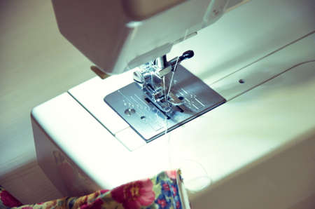 The process of processing fabric on a sewing machine closeup Stock Photo - 129386729