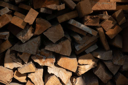 Wooden chopped firewood lies in a pile