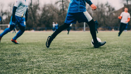 Soccer game with blurred background. Teams play soccer on green grass. Blurred background, defocus.