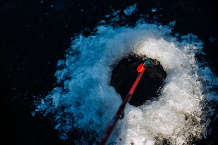 A man is fishing on the ice in the winter.