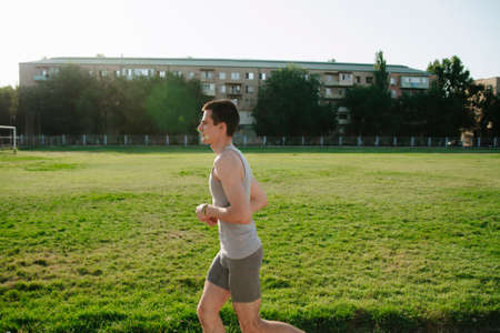 Male athlete jogging at outdoor stadium.A young man runs in a stadium on a sunny day in summer. Morning run in a stadium Reklamní fotografie