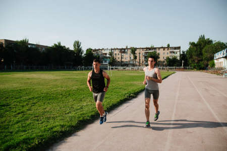 Young men jogging at the stadium.Young men running in a stadium on a sunny summer day. Morning run in a stadium