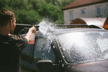 A man sprays a cleaning agent with a high pressure washer on a car. The car washes with a means of washing. The machine is in foam Stock fotó - 140227366
