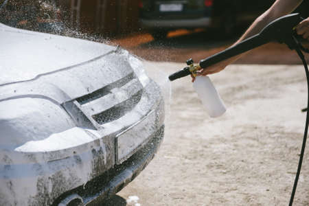 A man sprays a cleaning agent with a high pressure washer on a car. The car washes with a means of washing. The machine is in foam Stock fotó - 140228842