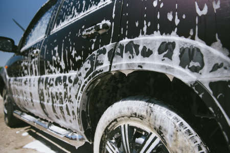 Machine in the foam. Car wash. Car in the foam from the cleaning agent. Parts of the machine in the relics