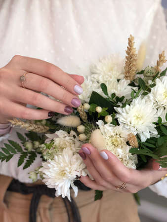 Woman with flesh-colored manicure with design. Fresh-colored female manicure on nails
