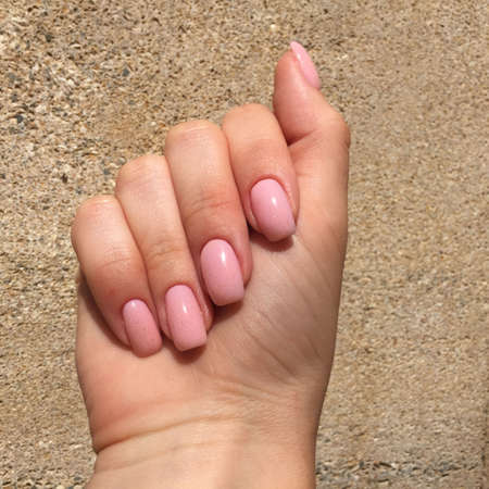 Closeup of hands of a young woman with pink manicure on nails against brown background Imagens