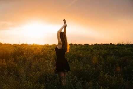 Fröhliche junge Frau im weißen Kleid, die durch schönen Lavendel geht, der im Sommer bei goldenem Sonnenuntergang abgelegt wurde Standard-Bild