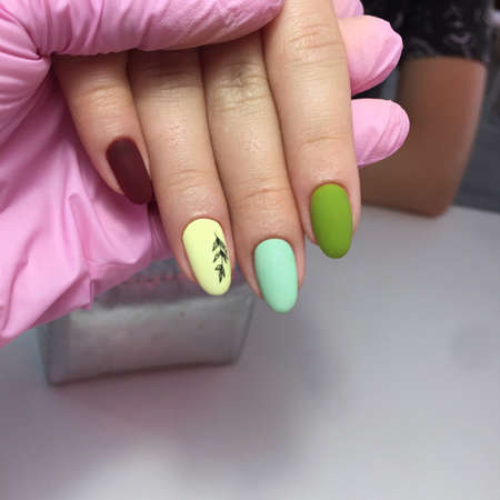 Multi-colored pastel manicure combined tone on tone with a striped background.Beautiful manicure closeup. Luxurious manicure on nails. Nails in different colors. Hand Care.