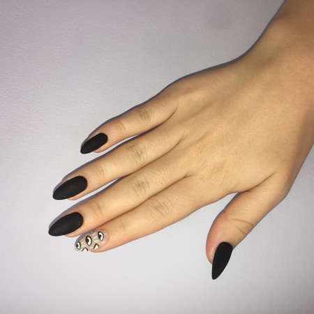 Woman with black manicure and pattern. Black matte female manicure on nails. Imagens
