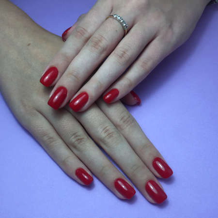 Closeup of hands of a young woman with red manicure on nails against blue background