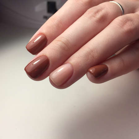 Woman with flesh-colored manicure with design. Fresh-colored female manicure on nails Imagens