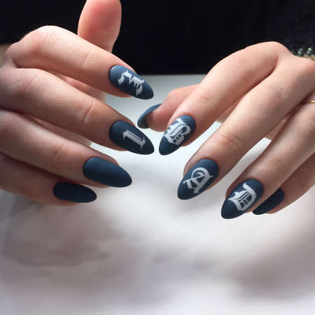 Woman with flesh-colored manicure with design and the inscription BAD. Fresh-colored female manicure on nails