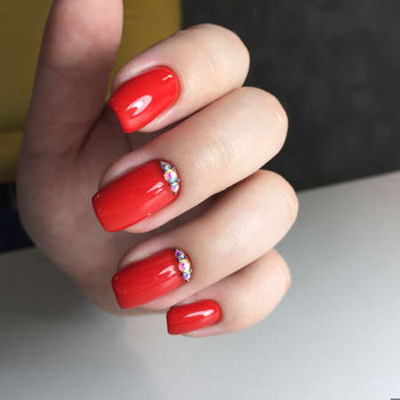 Closeup photo of a beautiful female hands with red nail.Beautiful female hands with red manicure on a dark background Imagens