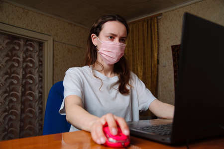 Young businesswoman in a medical protective mask works from home at the computer during self-isolation and quarantine. Virus coronavirus outbreak, flu epidemic and covid ncov novel. Stay home