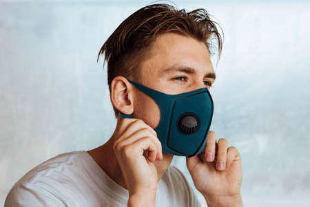 young man putting medical mask on face as protection against contagious disease like coronavirus