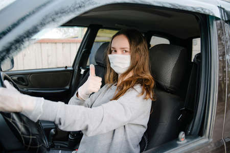 A woman driving a car in a protective mask and gloves.Prevention of coronavirus infection.Protective measures against coronavirus, covid-19 Banque d'images