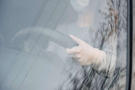 A woman driving a car in a protective mask and gloves.Prevention of coronavirus infection.Protective measures against coronavirus, covid-19 Stock Photo