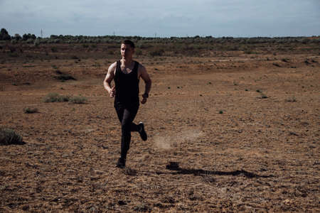 Runner athlete running in desert. Fit man training cardio outdoors. Summer sport fitness run in desert landscape. Фото со стока - 147082379