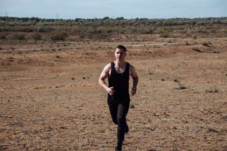 Runner athlete running in desert. Fit man training cardio outdoors. Summer sport fitness run in desert landscape.