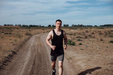 A man in sportswear and headphones runs along a dirt road in the summer