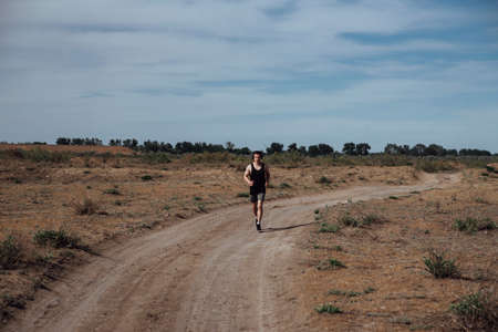 A man in sportswear and headphones runs along a dirt road in the summer Фото со стока - 147040512
