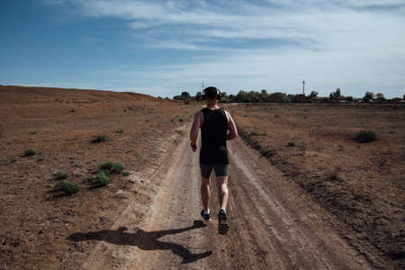 A man in sportswear and headphones runs along a dirt road in the summer Фото со стока - 147040862
