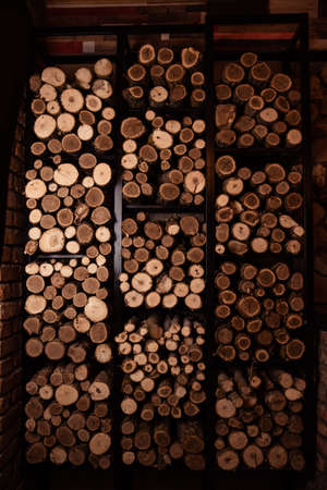 Firewood wall. Fuel for stove heating. Wooden firewood stacked wall. Natural wood background. Firewood stacked in several rows Standard-Bild