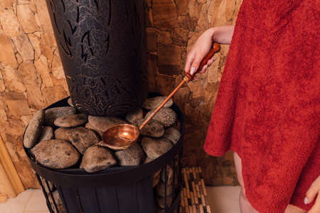 Woman hand pouring water into hot stone in the wooden traditional sauna spa room.