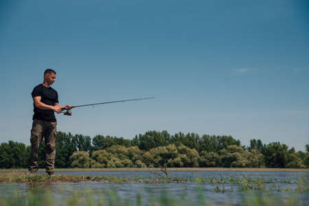 Fishing in river.Portrait of a fisherman with a fishing rod.A fisherman with a fishing rod on the river bank. Man fisherman catches a fish. Banque d'images