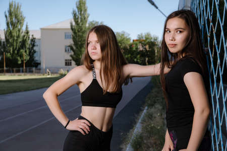 Two girls in sportswear posing at the stadium.Portrait of two sports girlfriends at the sports stadium.Sport and healthy lifestyle.