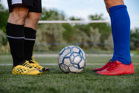 feet of soccer players before starting a match.Two football players stand near the ball on the football field Stock Photo